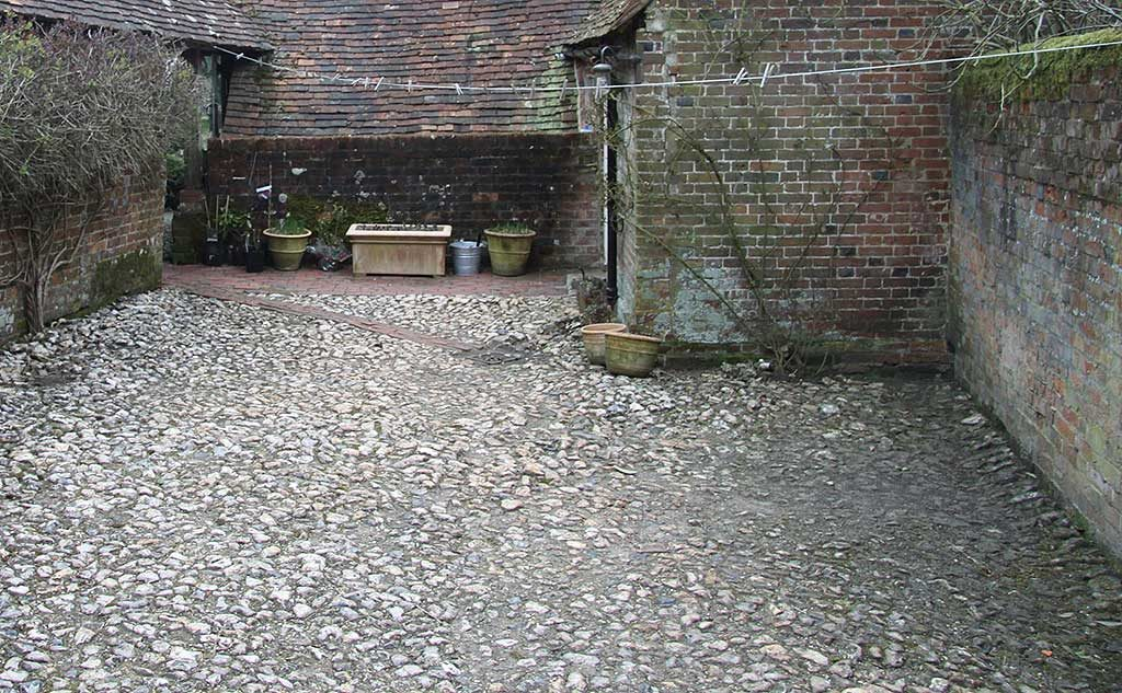 Flint courtyard showing damp edges where water collects